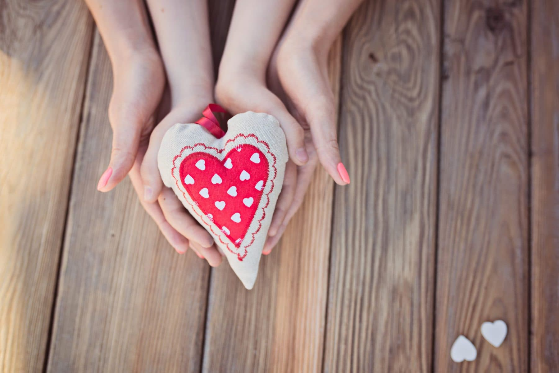 Child and mother's hands holding heart over a wooden table. Mothers Day, health care concept.