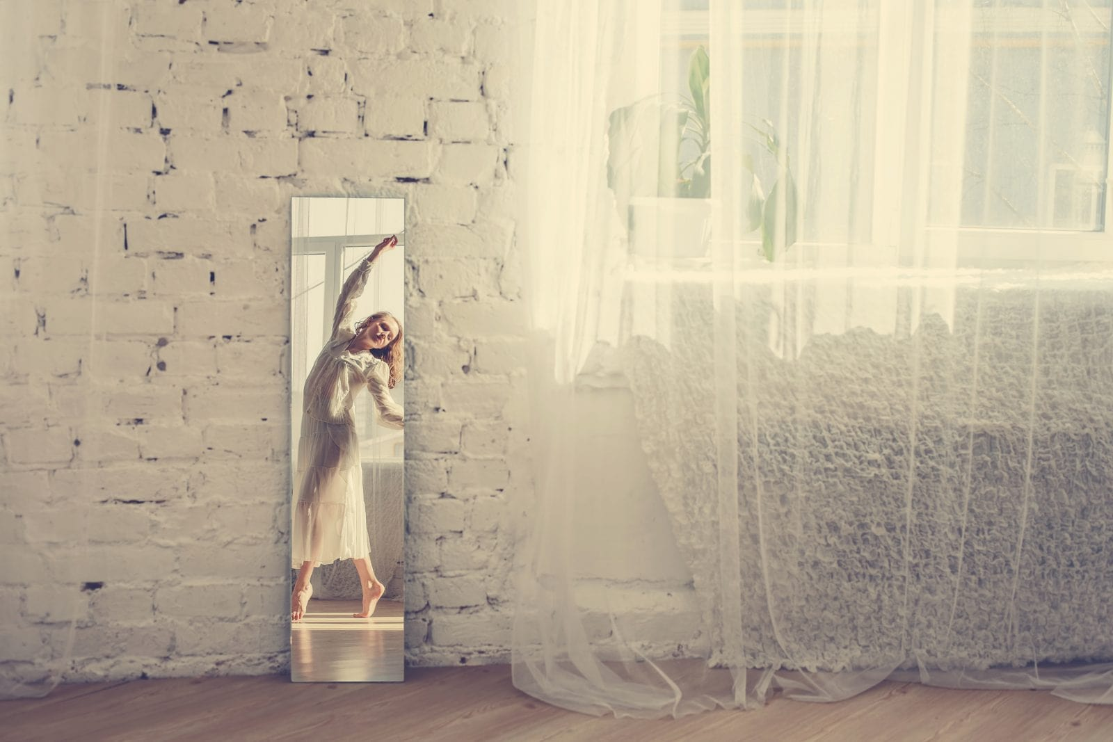 Beautiful  woman in white dress dancing in the bright interior. Reflection in the mirror