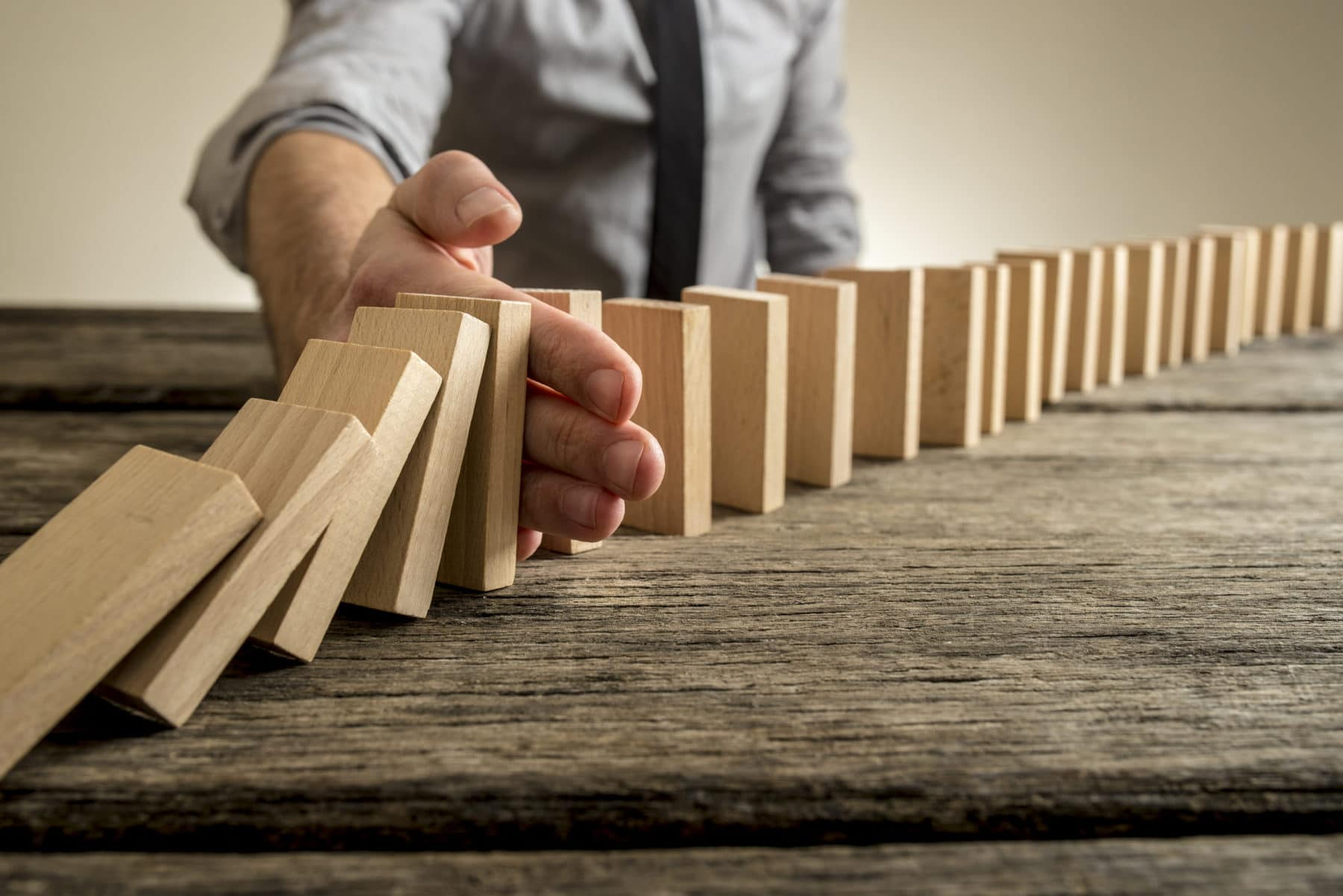 Man stopping domino effect on wooden table. Business success concept. Copy space.