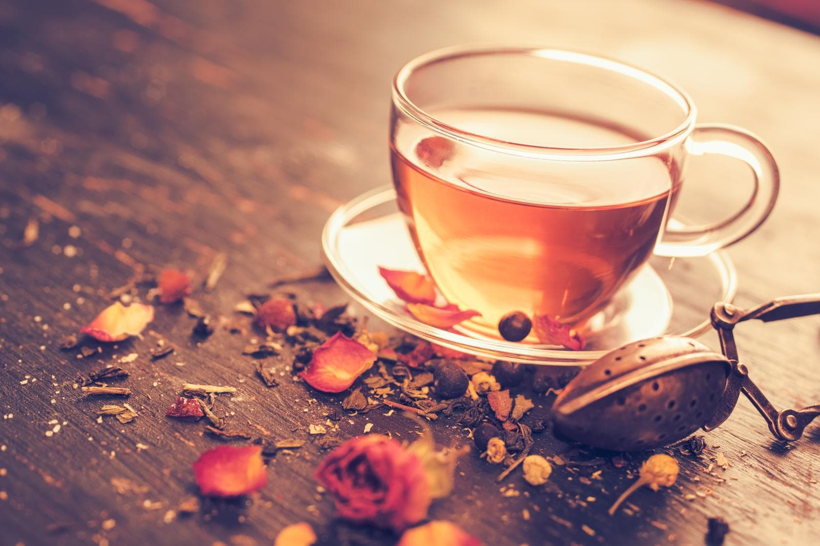 Freshly brewed tea, glass tea cup with dry rosebuds. Dry tea and tea cup on an old wooden table. Vintage toned