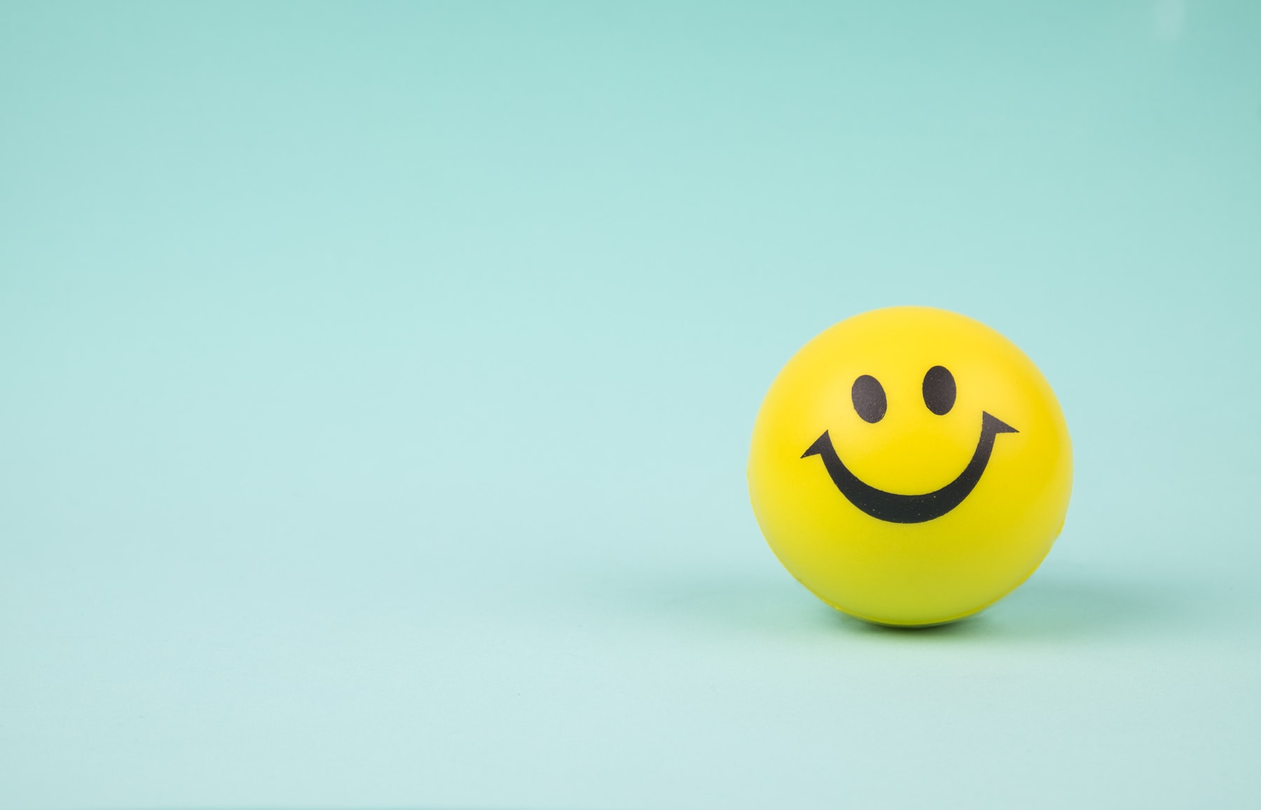 Yellow laughing happy smile face. Smiley face ball on background sweet retro vintage color.