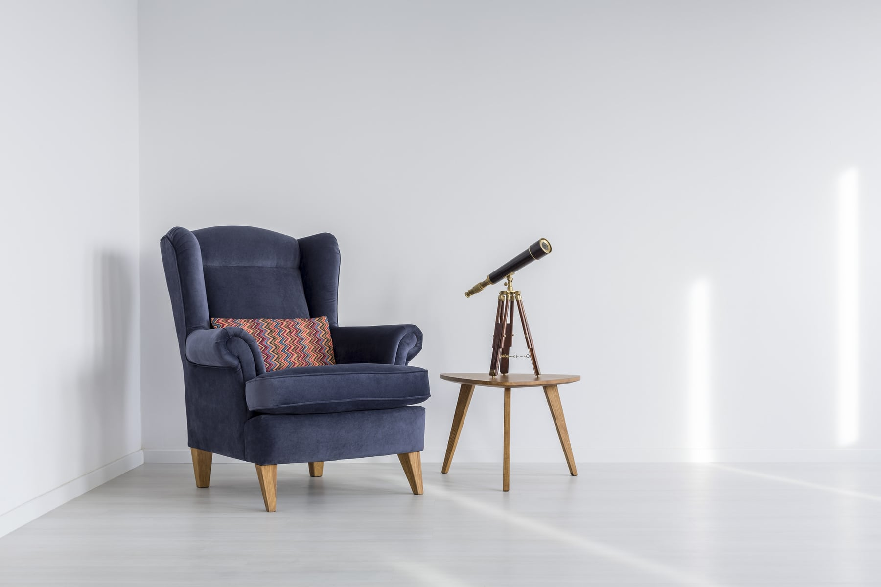 Telescope in small coffee table in cozy space with armchair