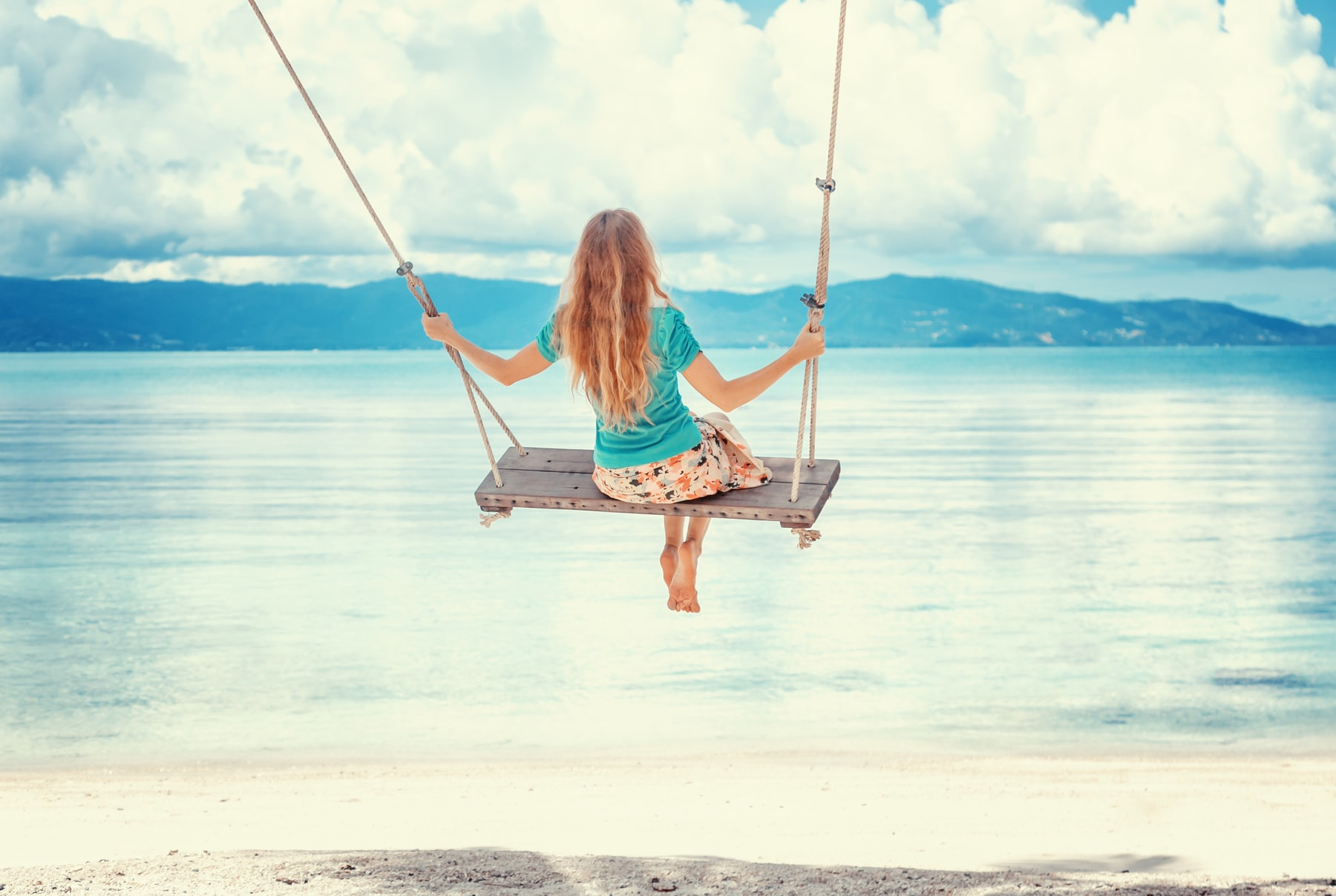 Young woman with long blond hair swinging on a swing on the shore of the tropical sea