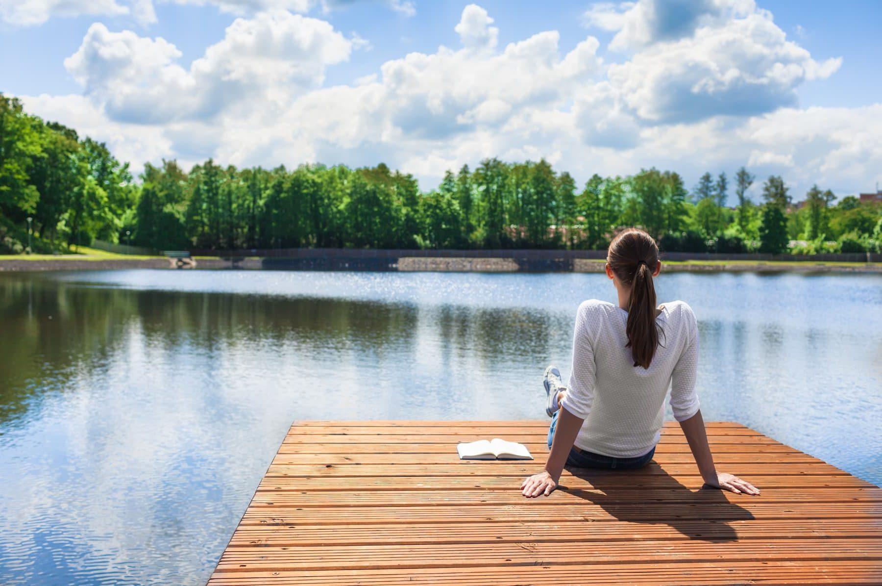 Woman relaxing by a beautiful lake.