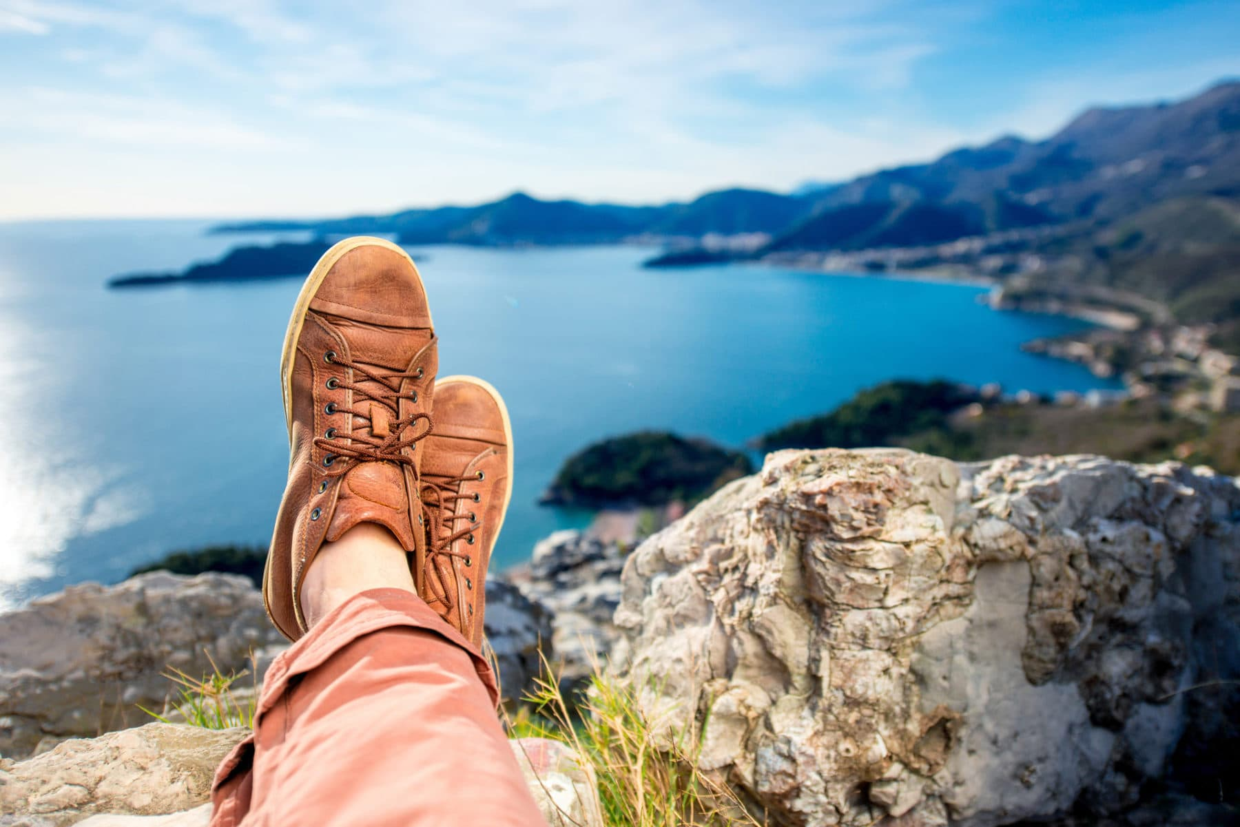 Men's legs in the brown shoes lying on the mountain on the sea scape background