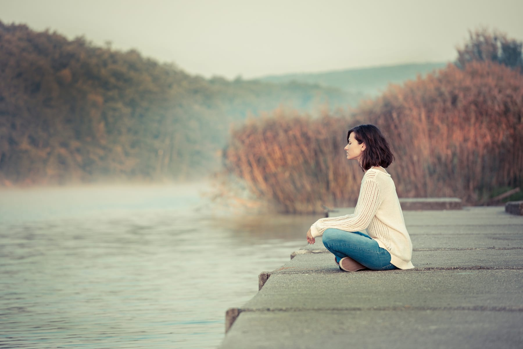 Relaxation by lake. Young woman sitting and looking away. Chilly morning.